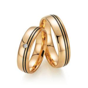 Goldene Eheringe mit zwei schwarzen Streifen