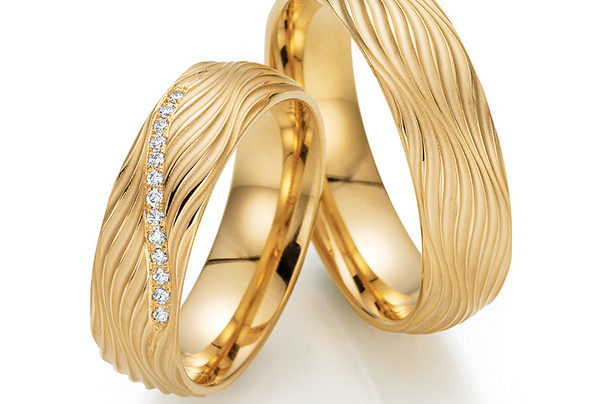 Goldene Eheringe mit Wellenmuster